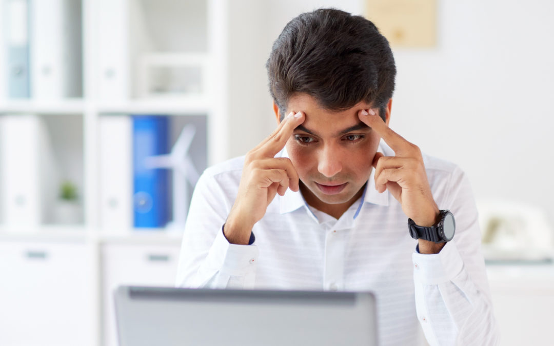 Man with a look of frustration as he looks at a computer